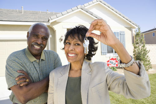 Couple smiling holding keys to their new home.