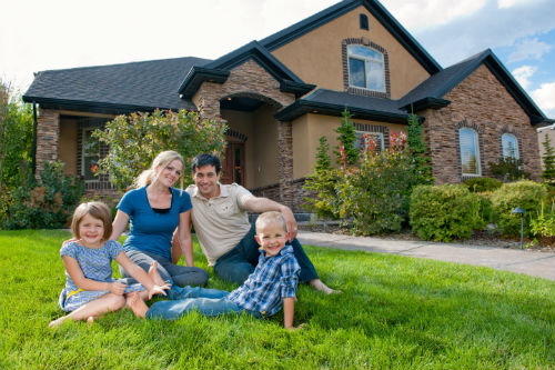 Stock image of a family on the lawn in front of a house