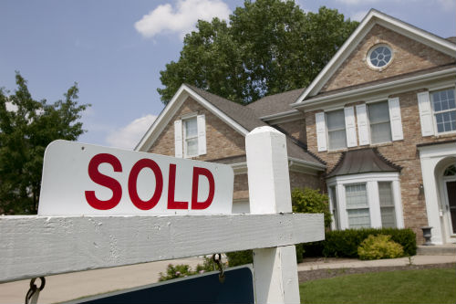 Stock image of a house with a SOLD sign in the yard