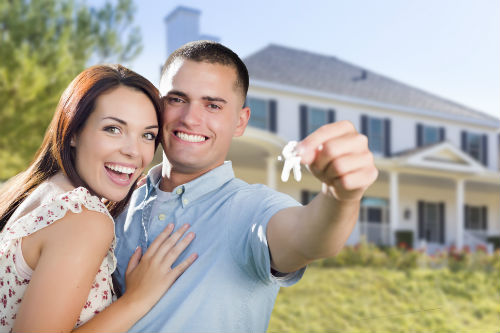 Stock image of a young couple holding a set of keys